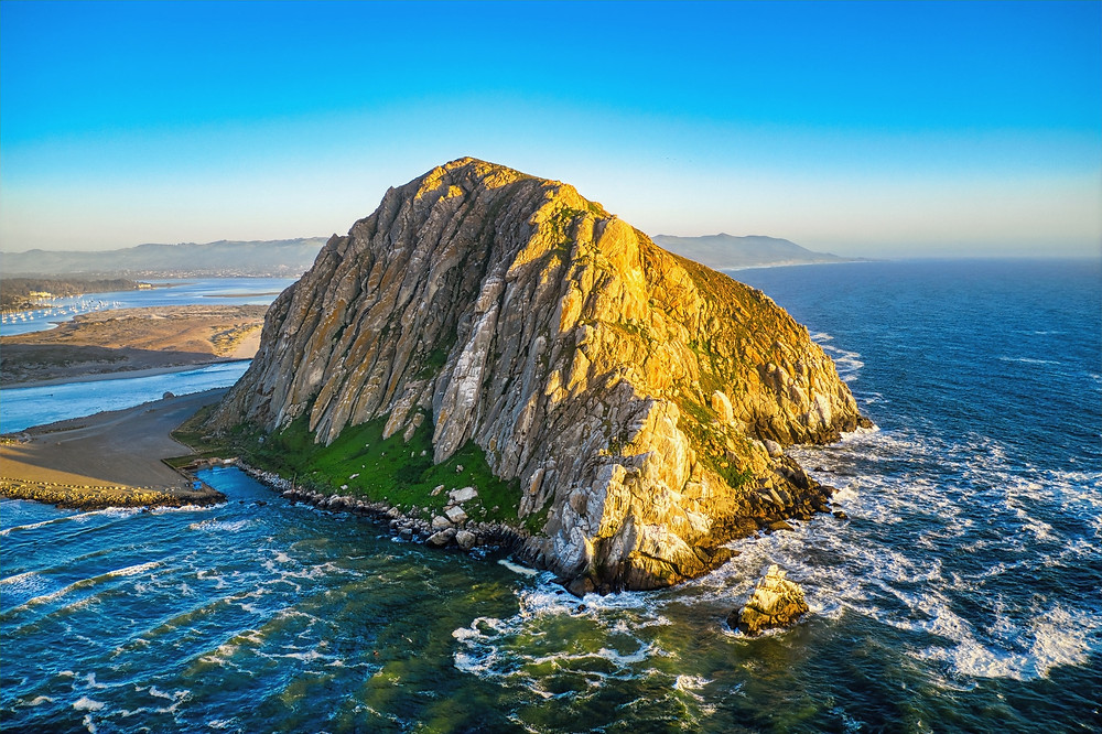 Morro Rock is a volcanic plug in Morro Bay, California, on the Pacific Coast at the entrance to Morro Bay harbor.