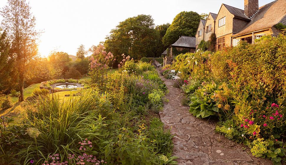High Glanau garden Wales sunset flowers plants summer arts crafts house path sundial pond alliums John Campbell photographer hosta landscape view
