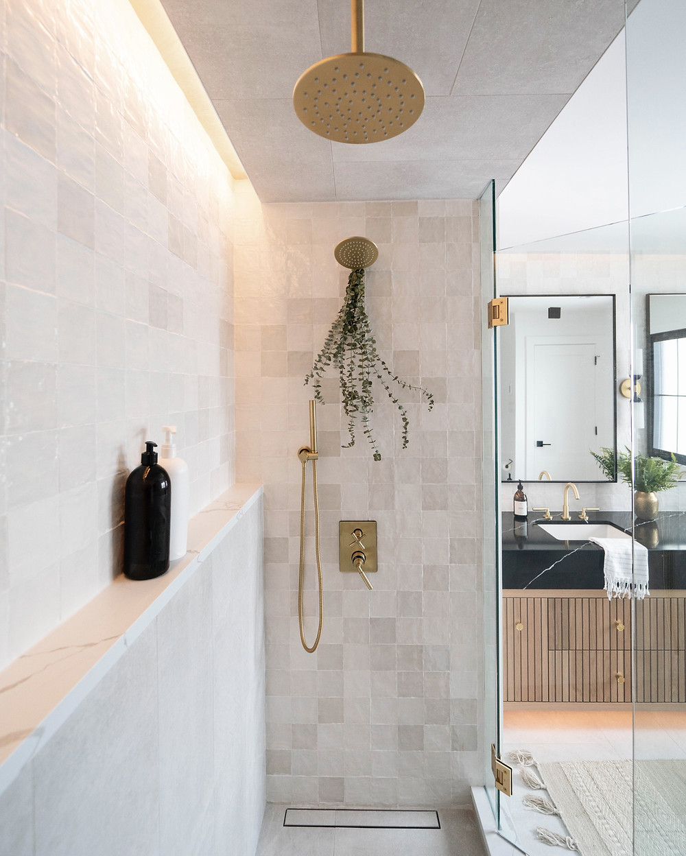 Riad textured tile makes a statement in this spa like ensuite bathroom seen in the Leclair Home. Beautiful brass fixtures and integrated lighting showcase this tiles natural texture