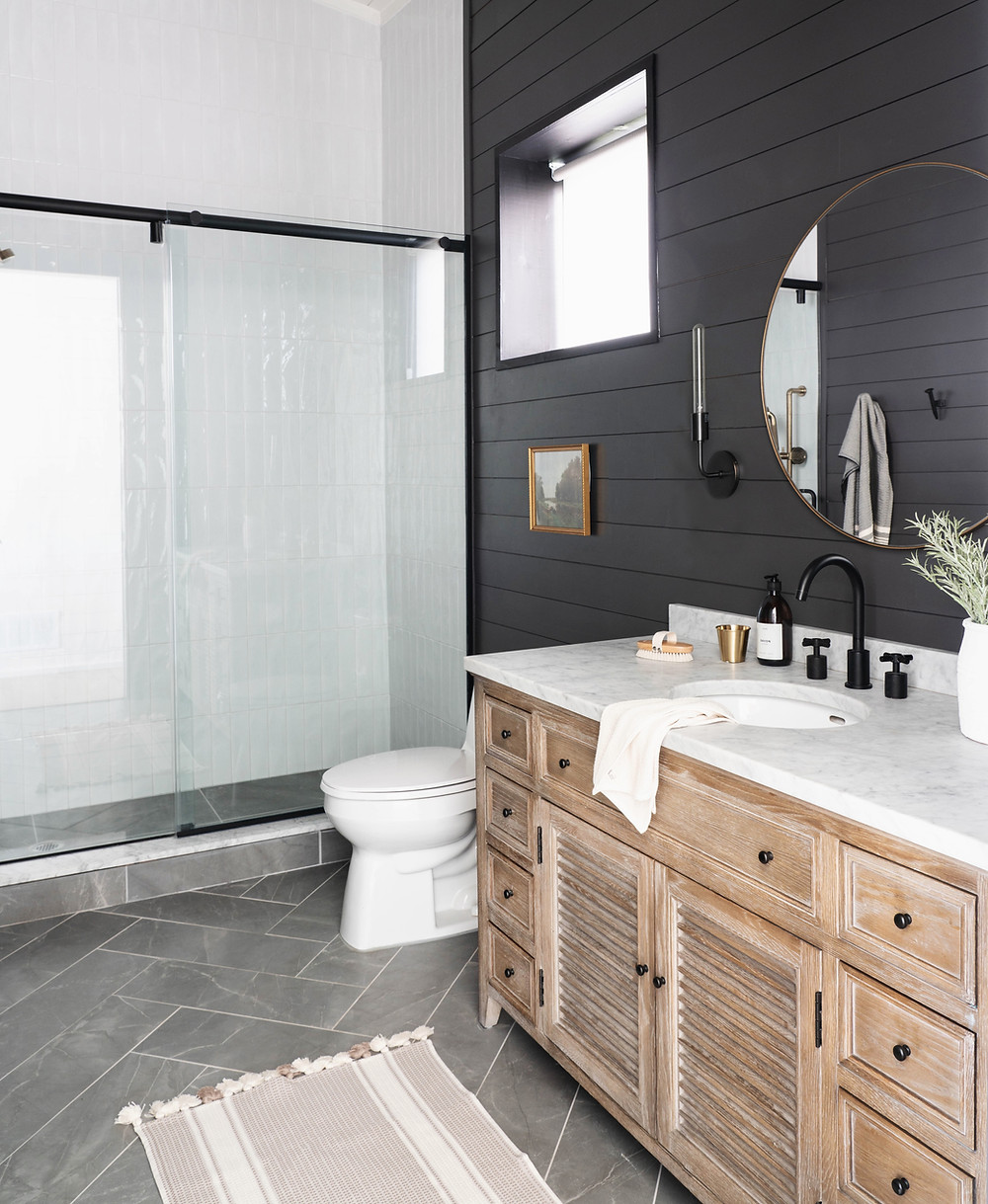 Moody dark shiplap walls and white clean tile contrast one another in this bathroom design by Leclair Decor