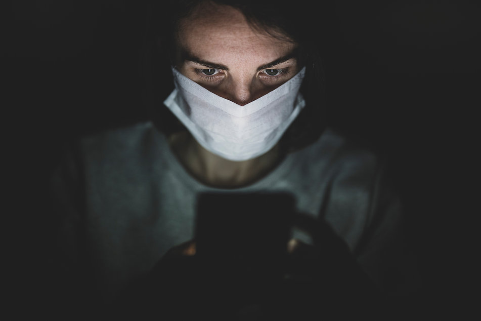 man-wearing-face-mask-using-his-phone-in