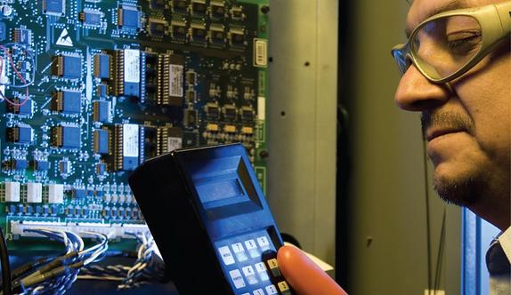 Elevator mechanic working on elevator electronics for maintenance