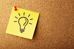 Post it note with light bulb drawn on it pinned to cork board