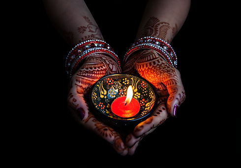 Woman hands with henna holding lit candl