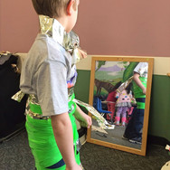 Child in creative green outfit looking in the mirror