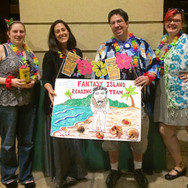 TCPL staff in tropical shirts and leis holding a sign