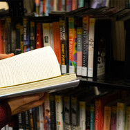 Person reading book in front of book shelves
