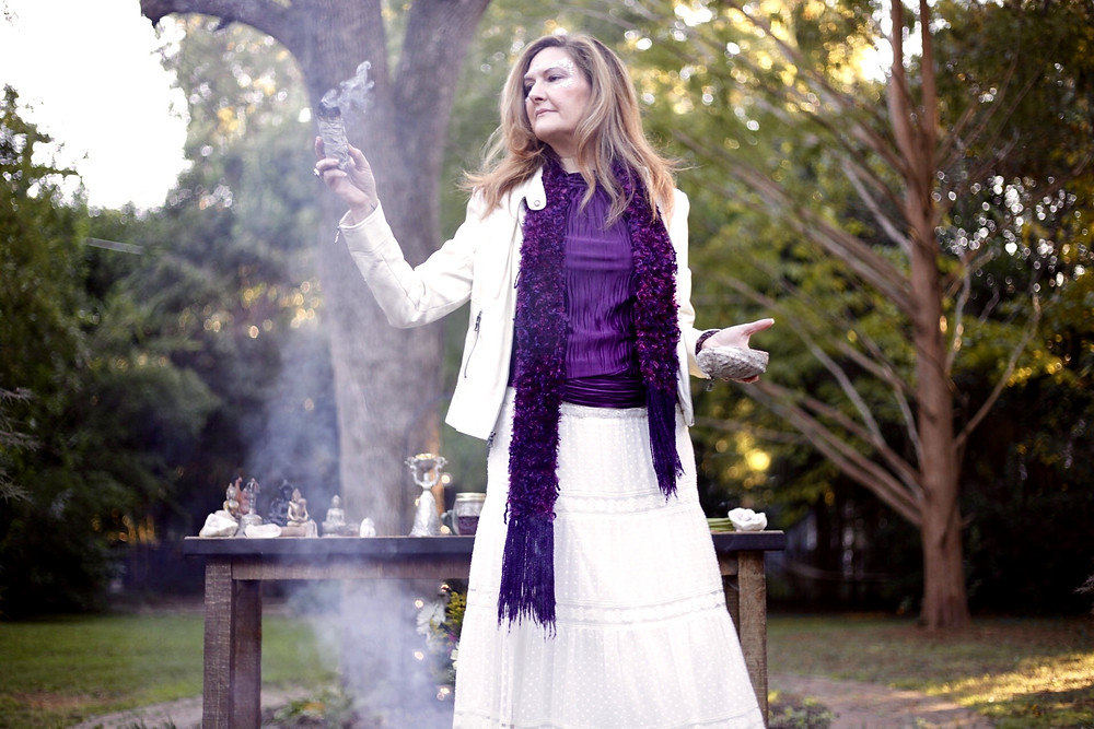 Mary the Metaphysical Maven, dressed in light cream and purple. Burning sage, channeling The Grandmother, and blessing the wedding space.