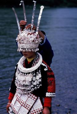 Miao girl in silver headdress by river Final