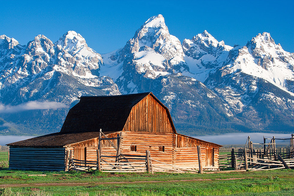 Wooden barn and Wyoming snowy mountain peak in the background