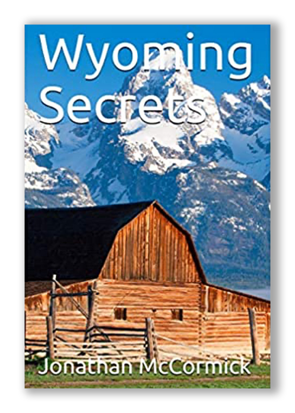 Wyoming Secrets, A book by Author Jonathan McCormick, book cover with wooden barn and Wyoming snowy mountain peak in the background