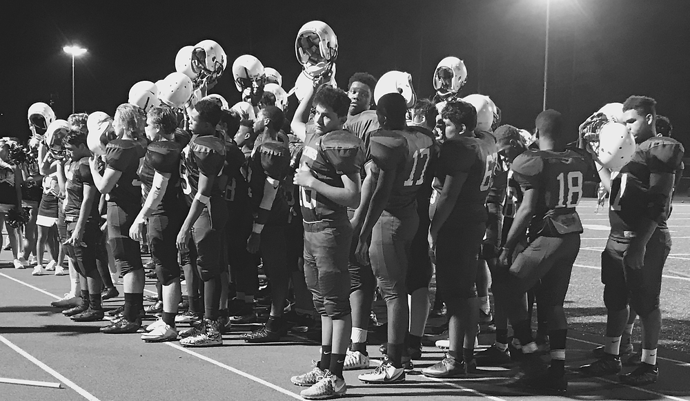 Lakeside Strong: The team stands together after their loss against Dunwoody, holding up their helmets during the Alma Mater (Photo by Joyce Johnson)