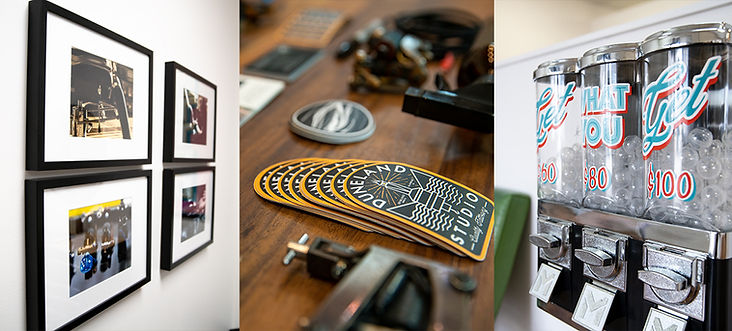 Artwork from Duneland Studio's artists Joe Fryday and Steve Florer hanging on a white wall | Duneland Studio stickers on a wooden desk surronded by tattoo machines | Gumball machines Get What You Get and prices at Dunelan Studio