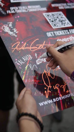 A participant signing the Gathering II poster