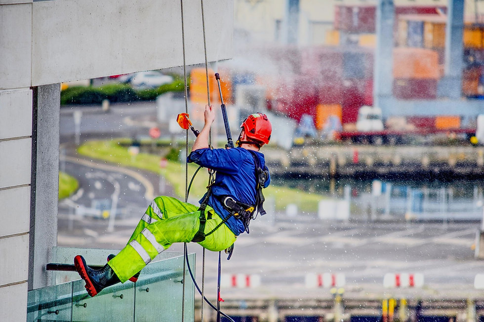 Abseiler power washing building in Belfast
