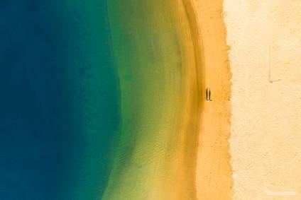 -- pláž v Puerto Mogan, Gran Canaria --   Prosincové ráno. Čili sluníčko dělá dlouhé stíny ještě v době, kdy správná noční sova teprve odkládá hrnek s dvojitým espressem, startuje drona a jde se proletět podél pobřeží.   Tihle dva už kafe měli za sebou, jako jediní z celého ostrova asi. Za chvíli už bude na pláži plno, stíny budou mít po postřižinách a můj dron bude zpátky na balkóně.   A já si jdu ještě lehnout. Vždyť jsou vánoční prázdniny.