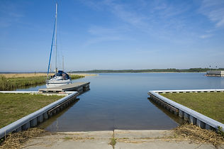 Launch ramp on the lake with moored yach