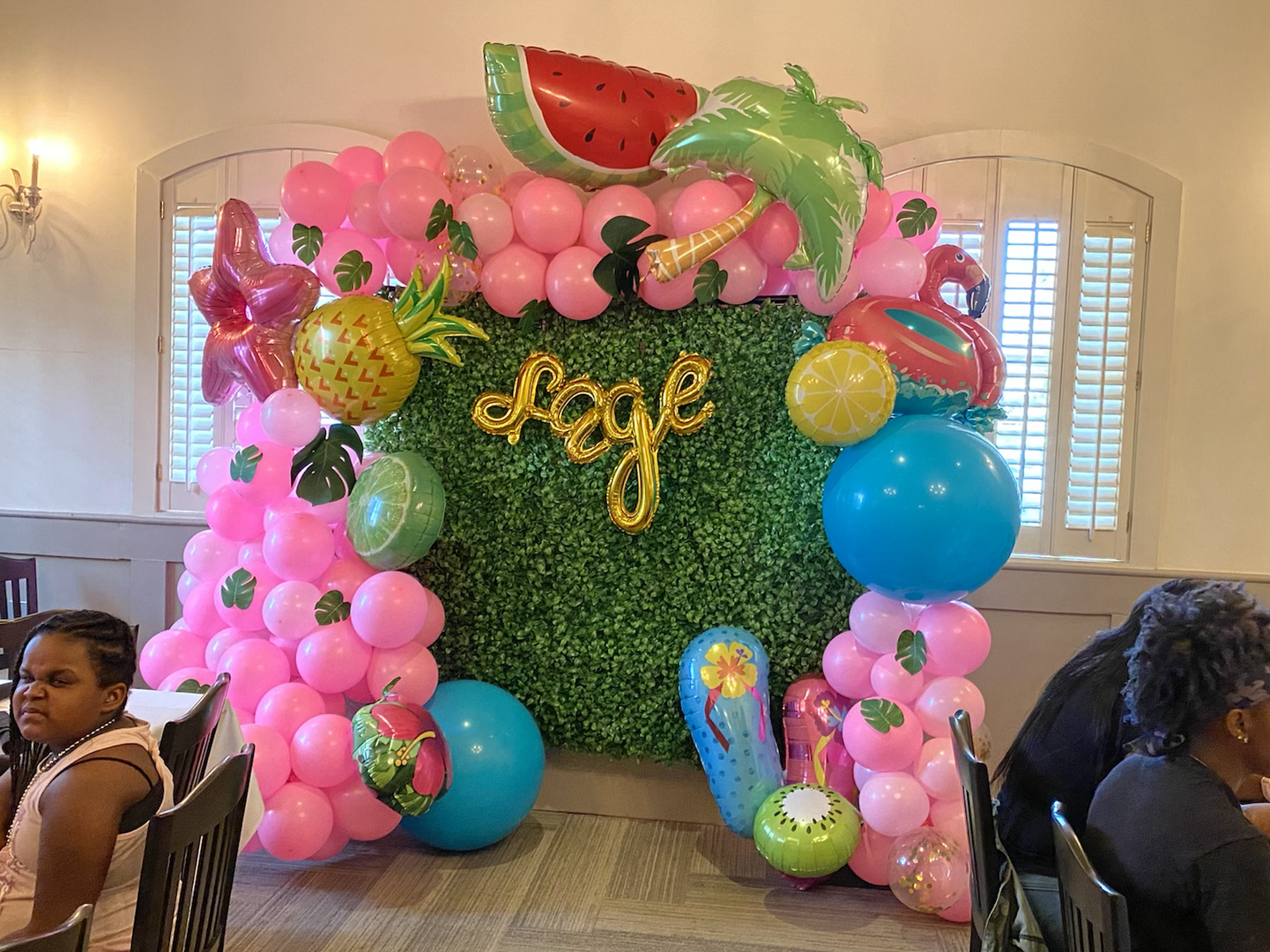 Tropical Themed balloon arch w/boxwood hedge backdrop