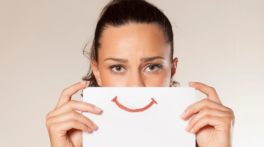 Mulher segurando placa de sorriso