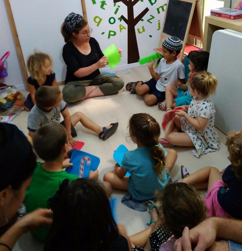 מורה בעמותת א.ה.ב.ה. מלמדת אנגלית לילדי גן