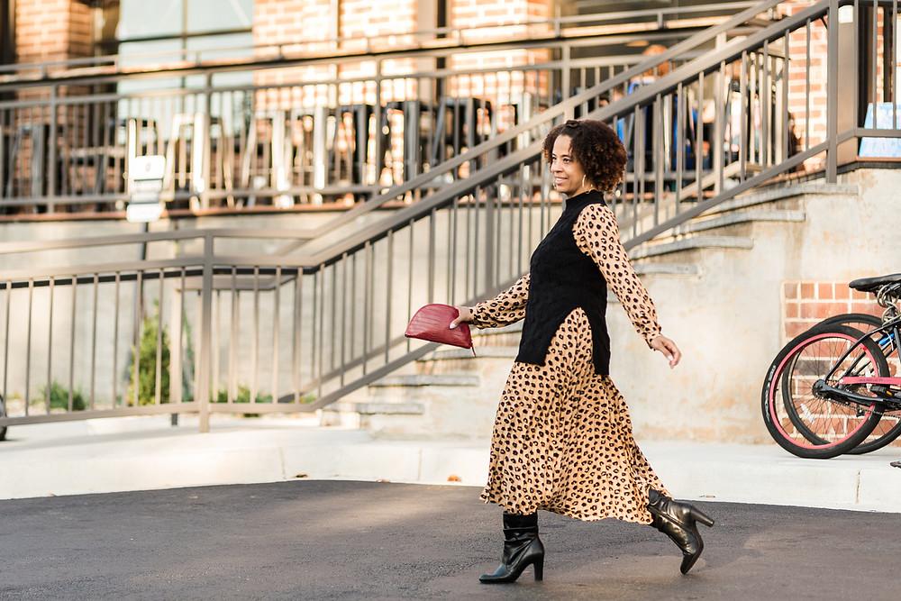 A black woman walking in a leopard print dress. she is smiling