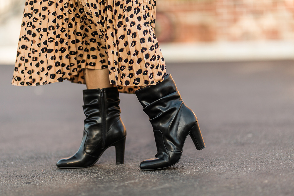 A woman wearing fashionable black boots perfect for Fall