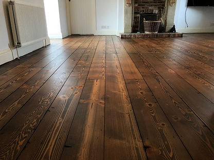 Dark Oak stained Pine floorboards in a living room.