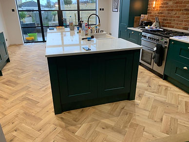 Oak parquet flooring around modern green kitchen island.