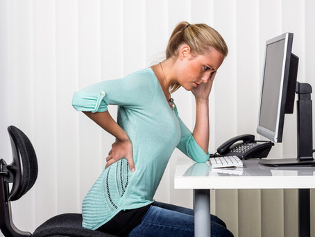 Why is sitting for prolonged periods bad for our backs?