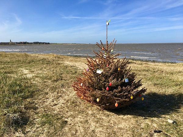 Weihnachtsbaum am Strand mit Ostereiern