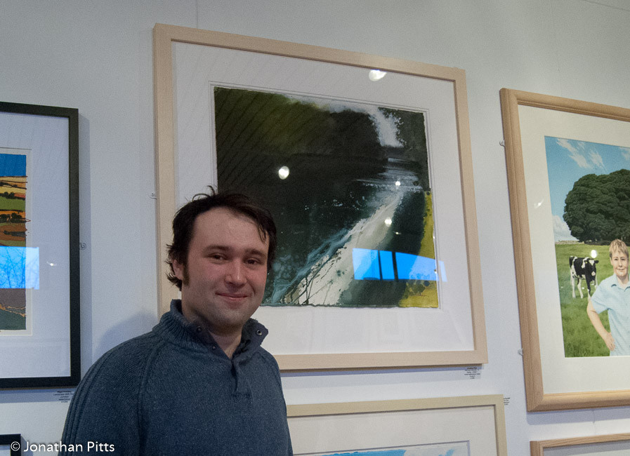 Jonathan Pitts at the Royal Watercolour Society Contemporary Watercolour Exhibition in front of his mixed media painting Afternoon meander nr. Henley.