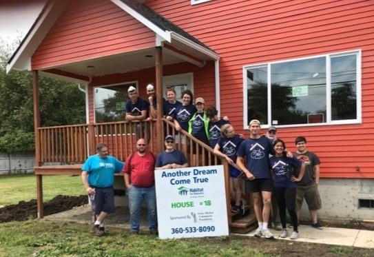 volunteers standing in front of in-progress Habitat house build