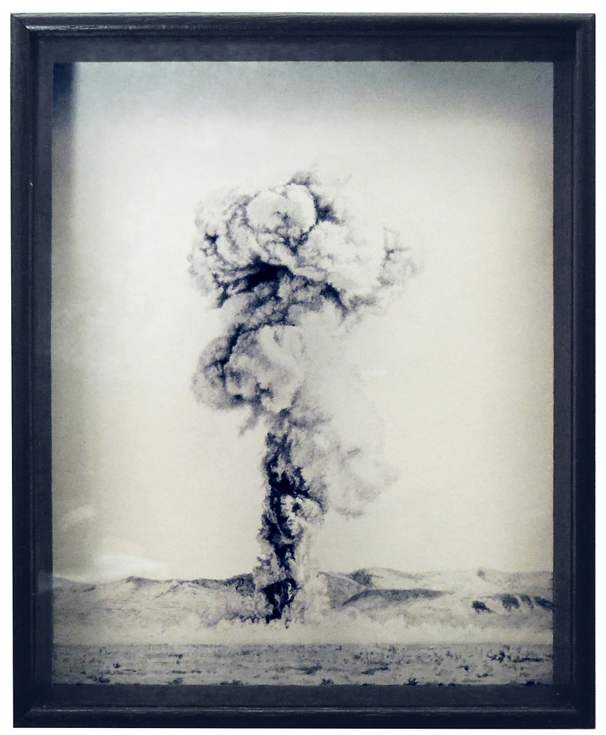 A monotone image of an oil painting on glass of an atomic explosion in the nevada desert. Close up and delicately painted with a dark wooden frame. Size 10 x 8 inches in real life. Painted by Kirsty Harris.