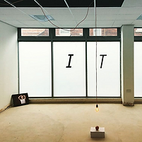 "An installation image of an exhibition called ""Who wants flowers when we're dead?"" it depicts a large window with the vinyl text ""IT"" and in the corner sits a screen playing Artist Lizz Brady's video piece. Kirsty's artwork ""The Apple"" is a stack of A4 paper printed with instructions to eat the apple which sits on top. A lightbulb on a long cable hags low and directly above it illuminating the work. It references J. R. Oppenheimer's attempt to poison his tutor at Cambridge university."