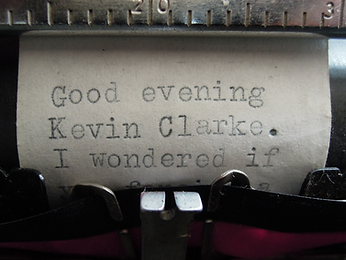 An image of a close up of a typewriter that has typed Good evening Kevin Clarke. I wondered if. This links to a page for the artists Harris and Clarke who collaborate on performance art events.