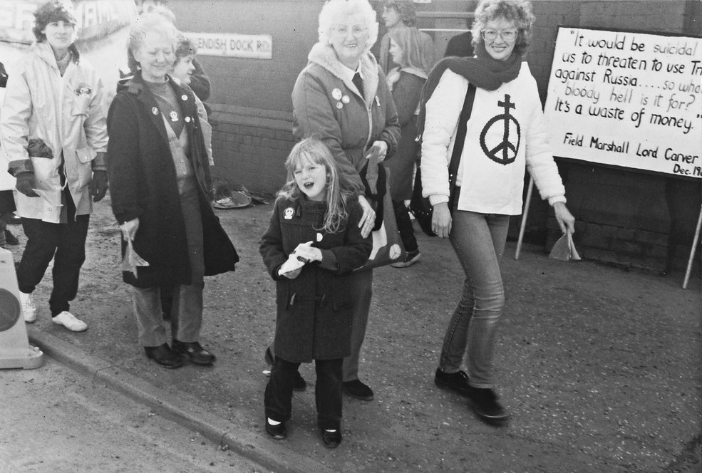 A black and white photograph from the 1980s. In it is a 6 year old Kirsty with her mother and grandma and other protestors on a CND march. She wears a duffel coat and big CND badge. The adults in the photograph smile while the child is looking defiantly at the camera saying something. Kirsty's mother wears a large tabard with a CND sign topped with a cross. In the background a protest sign can be seen reading: It would be suicidal for us to threaten to use trident against Russia, So what the bloody hell is it for? it's a waste of money.