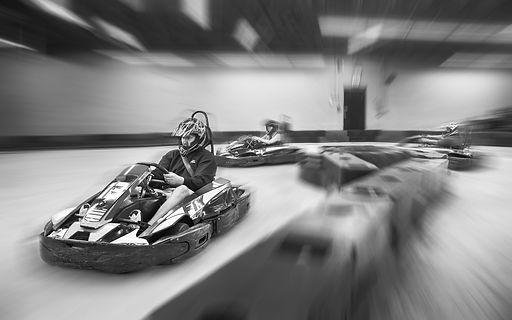 Man and woman driving go karts