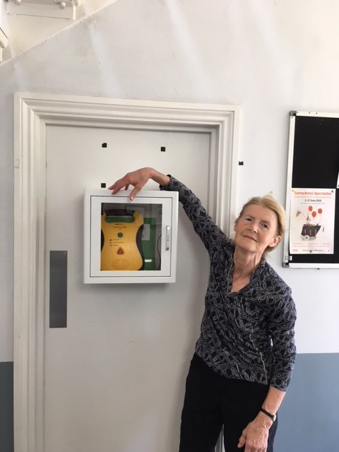 Margaret next to the new defibrillator in the main hallway.