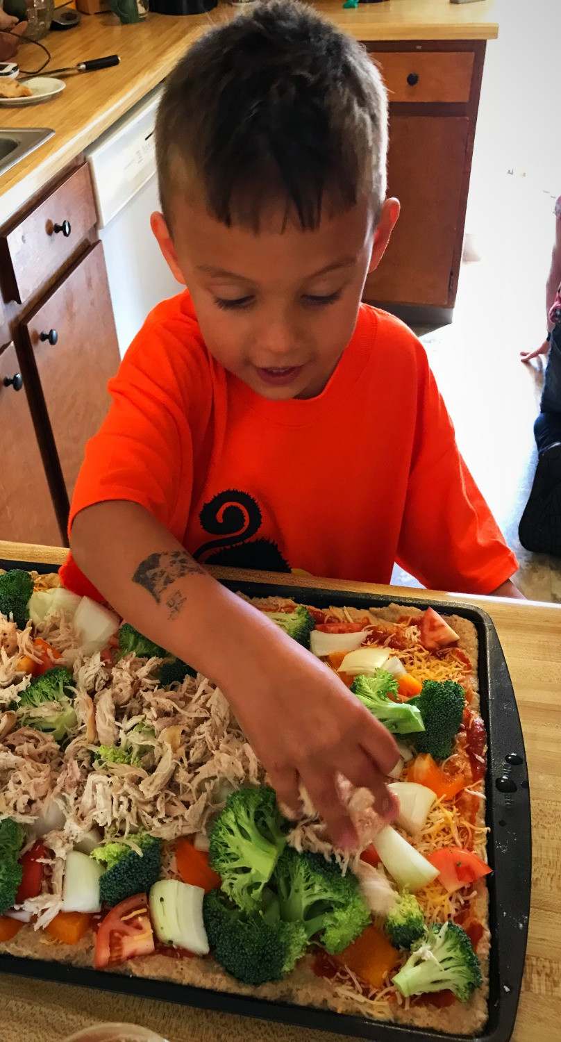 Child adding healthy toppings to a pizza