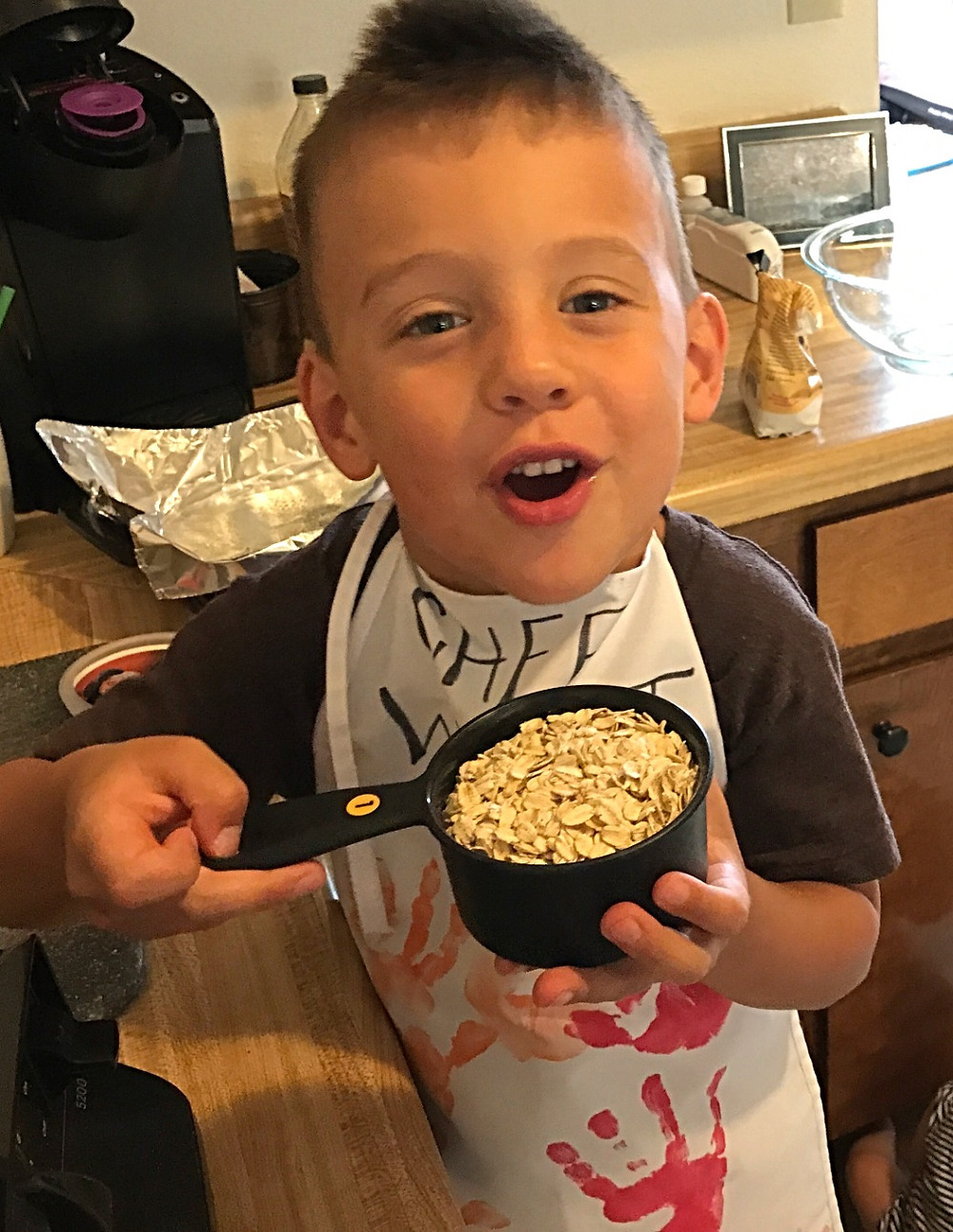 Child holding oats in measuring cup