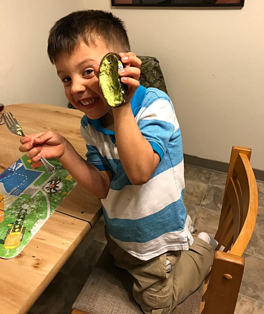 Child holding healthy avocado