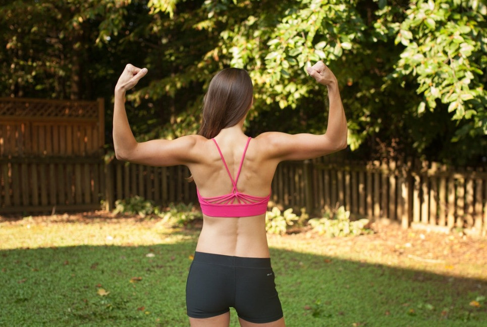 Athletic woman flexing arm muscles