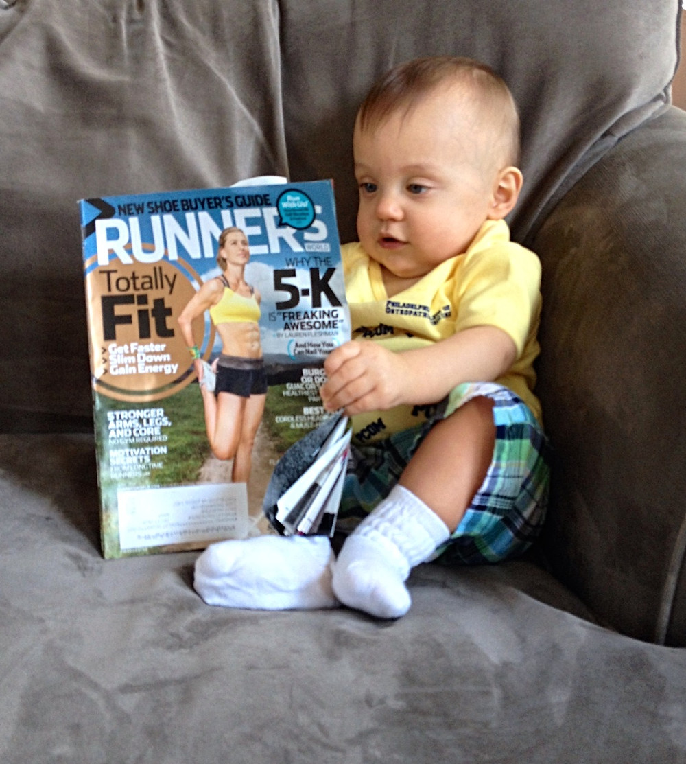 Baby boy reading running magazine