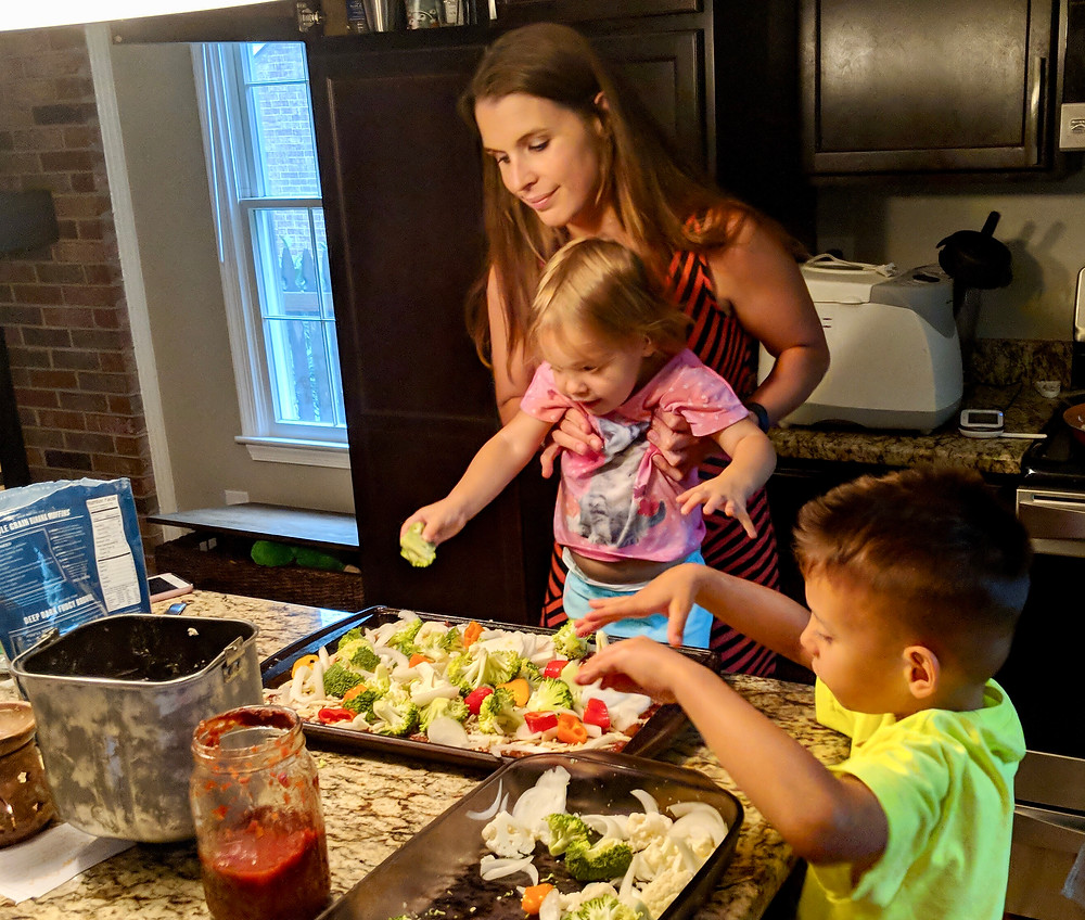 Family making healthy pizza together