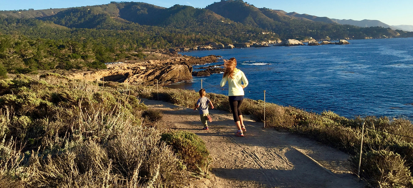 Mom Running With Son By Ocean