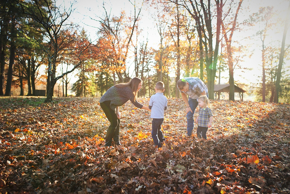 Family playing together in fall leaves