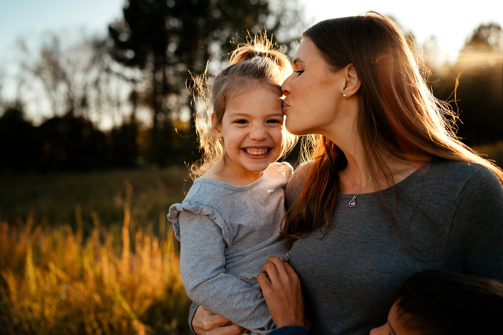 a strong military spouse kissing a healthy and happy child