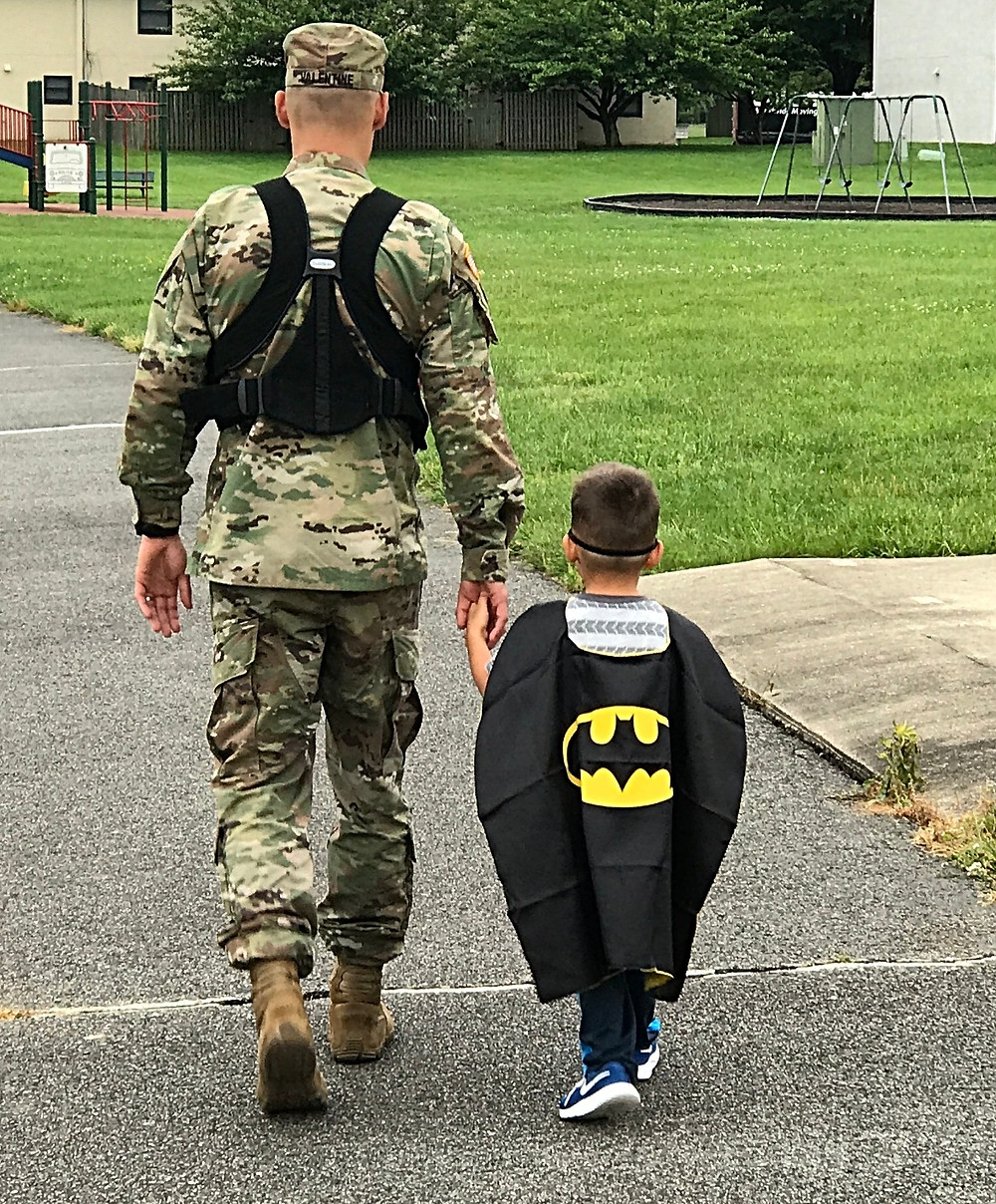 Soldier wearing baby holding toddler in batman costume's hand