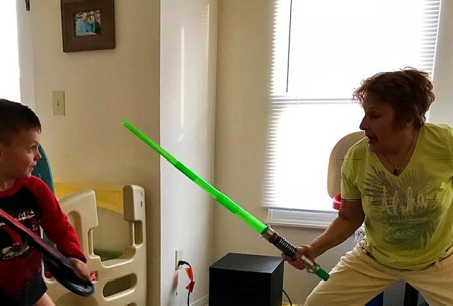 Grandmother having a light saber battle with grandson