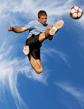 Giocatore di calcio colpisce un pallone al volo in salto